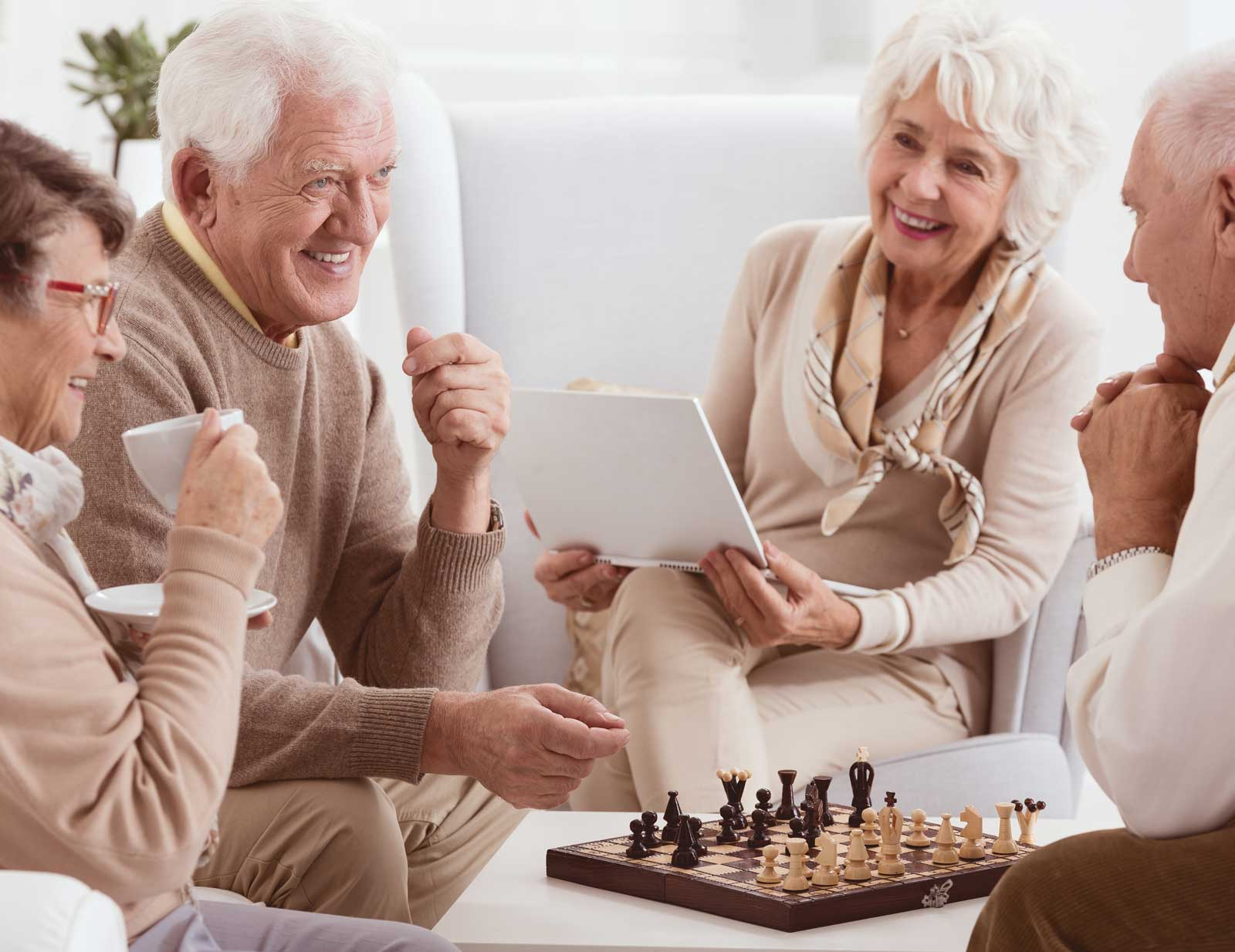 older couples playing chess and drinking coffee